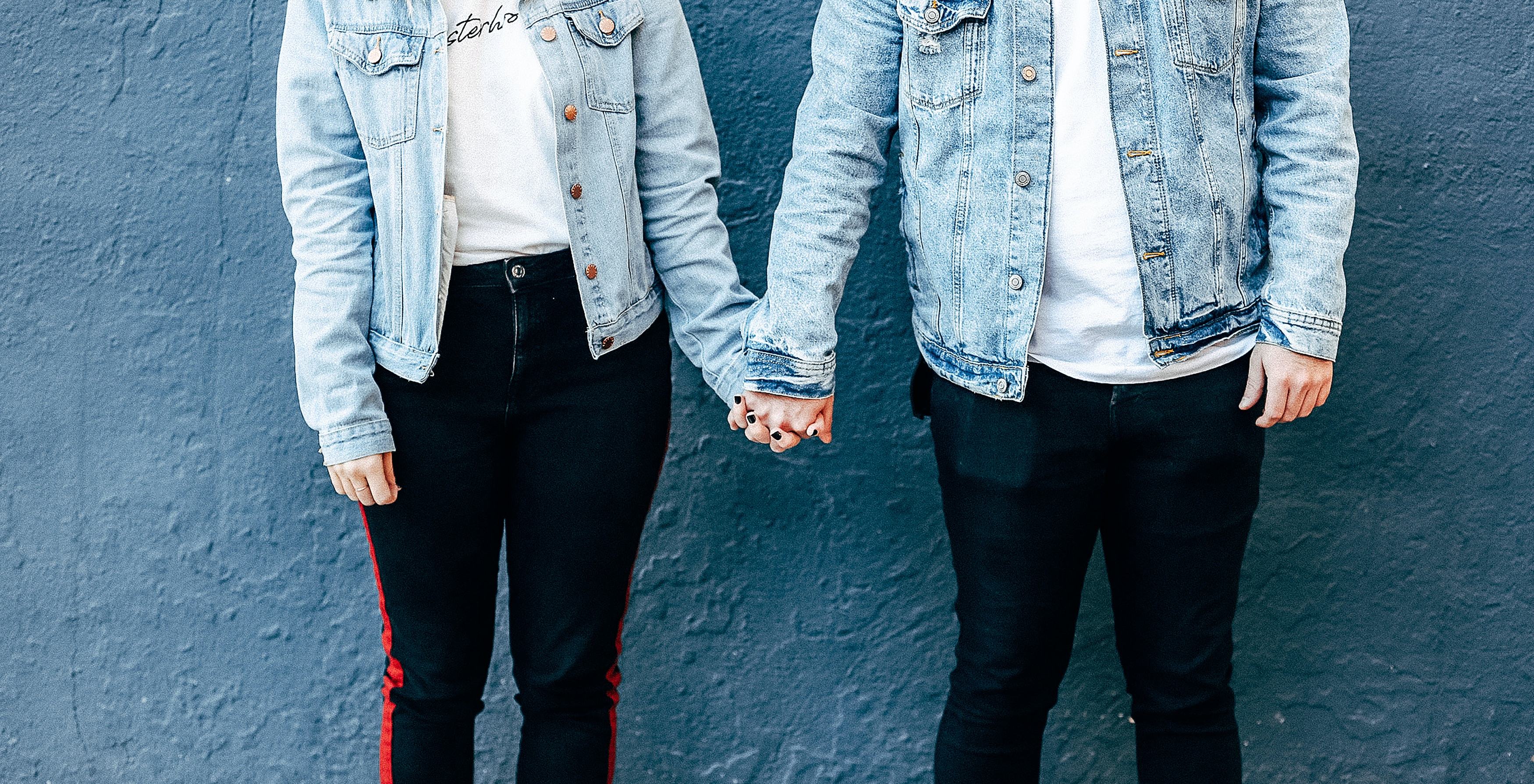 two-person-standing-and-holding-their-hands-beside-blue-wall-1769859